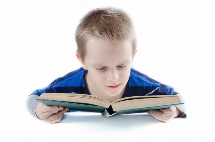 本を持って勉強する少年